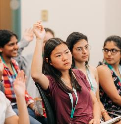 Participants raise their hands during a class session.